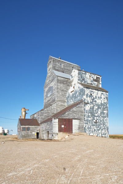 Plate 1. This building does not look tridimensional: the sun strikes it head-on with a sterile light that obliterates texture and does not shew shape, volume or depth, but in effect makes the grain elevator look like a cardboard cut out pasted on the frame.